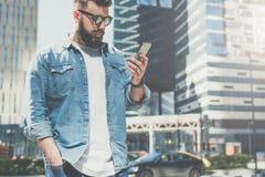 Junger bärtiger Geschäftsmann in der Sonnenbrille steht auf Stadtstraße und benutzt Smartphone Mann liest Informationen vom Telef Lizenzfreie Stockfotografie