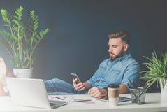 Junger bärtiger Geschäftsmann sitzt im Büro, wirft seine Beine auf Tabelle und verwendet Smartphone Stockfotografie