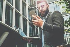 Junger bärtiger Geschäftsmann steht gegen modernes Gebäude, benutzt Smartphone und hält einen Laptop in seiner Hand Mannarbeiten Lizenzfreie Stockfotos
