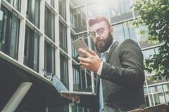 Junger bärtiger Geschäftsmann steht gegen modernes Gebäude, benutzt Smartphone und hält einen Laptop in seiner Hand Mannarbeiten Stockfotografie