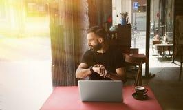 Junger bärtiger Geschäftsmann-Wearing Black Tshirt-Arbeitslaptop-städtisches Café Mann-sitzendes hölzernes Tabellen-Schalen-Kaffe Lizenzfreie Stockfotos