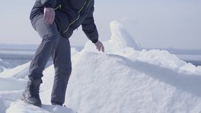 Junger bärtiger gut aussehender Mann in der warmen Jacke, im Hut und in den Stiefeln, die den Gletscher climbling sind Überrasche stock video