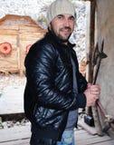 Junger bärtiger gutaussehender Mann mit Hut und Lederjacke unter Verwendung einer alten Waffe Stockfoto