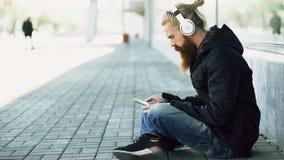 Junger bärtiger Hippie-Mann mit den Kopfhörern, die auf Straße sitzen und Smartphone für verwenden, hören auf Musik und das Inter Stockbilder