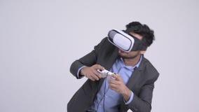 Junger bärtiger indischer Geschäftsmann, der Spiele spielt und Kopfhörer der virtuellen Realität verwendet stock footage