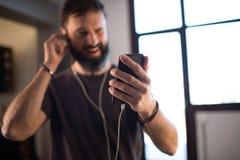 Junger bärtiger Kerl, der zufälliges graues T-Shirt hörende Musik in den Kopfhörern, soziale Netzwerke auf Smartphone überpr lizenzfreies stockbild