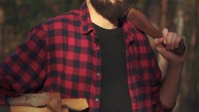 Junger bärtiger Kerlweg im Wald mit gehackt meldet eine Hand und Axt in seiner Schulter an Förster trägt Brennholz stock video