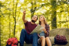 Junger bärtiger Mann, der einem Mädchen etwas im Wald zeigt Lizenzfreies Stockbild