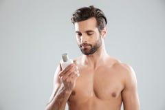 Junger bärtiger Mann, der Parfüm betrachtet lizenzfreie stockfotos