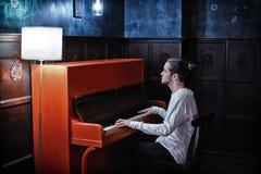 Junger bärtiger Mann, der rotes Klavier spielt Lizenzfreie Stockfotos