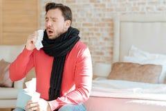Junger bärtiger Mann, der zu Hause unter Krankheit leidet Lizenzfreies Stockfoto