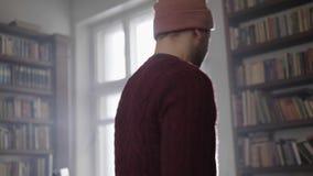 Junger bärtiger Mann im Braun strickte Strickjacken- und Sockenkappentanzen im Tageslichtraum stock video footage