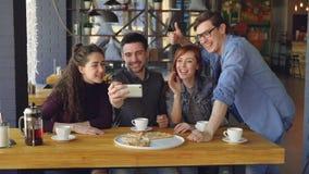 Junger bärtiger Mann macht Videoanruf vom Pizzahaus zusammen mit besten Freunden Die spielerischen Kameraden sprechen und lächeln stock footage