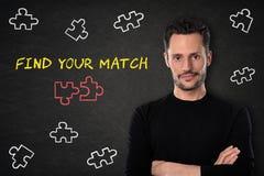 Junger bärtiger Mann mit den gekreuzten Armen, Puzzlespielstücke und Text 'finden Ihr Match 'auf einem Tafelhintergrund stockfotografie