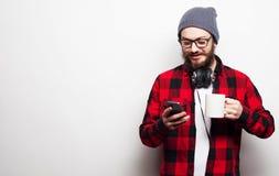 Junger bärtiger Mann mit Handy Stockfotografie