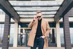 Junger bärtiger Mann mit moderner Frisur und modischer Mantelstellung nahe Geschäftszentrum lizenzfreie stockfotos