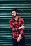 Junger bärtiger Mann, Modell der Mode, ein kariertes Hemd mit einem grünen Vorhang hinter ihm tragend lizenzfreie stockfotografie