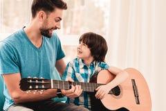 Junger bärtiger Vater Playing auf Gitarre mit Sohn stockfoto