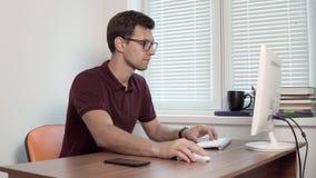 Junger Büroangestellter in den Gläsern, die am Fenster im Büro und in Schreibenbericht auf Computer sitzen Smartphone auf stock video