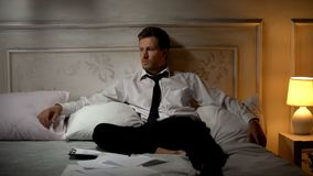 Junger Büroangestellter, der auf dem Bett, frustriert mit Beschäftigungsbeendigung sitzt lizenzfreies stockbild