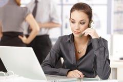 Junger Büroangestellter, der den Kopfhörer sitzt am Schreibtisch verwendet Stockfotos