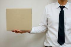 Junger Büroangestellter, der einen leeren Papierkasten hält Lizenzfreie Stockfotografie
