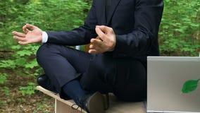 Junger Büroangestellter, der nach innen Harmonie, sitzend im Lotussitz entspannt findet stock video footage