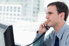 Junger Büroangestellter am Telefon Stockfoto
