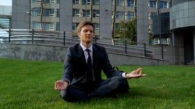 Junger Bürovorsteher, der im Lotussitz, meditierend auf Gras, Freiheit sitzt lizenzfreie stockfotografie