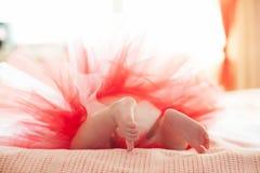 Junger Babyfuß Neugeborenes Mädchen im roten Kleid Stockbild
