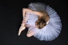 Junger Balletttänzer, der das pointe sitzt auf bindet stockfotos