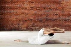 Junger Balletttänzer, der ihre Rückseite bei der Ausführung von Spalten verbiegt stockfotografie