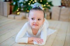 Junger Balletttänzer, der nahe Weihnachtsbaum liegt Lizenzfreies Stockbild