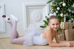 Junger Balletttänzer, der nahe Weihnachtsbaum liegt Stockfotografie
