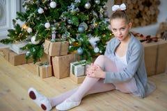 Junger Balletttänzer, der nahe Weihnachtsbaum sitzt Stockfotografie