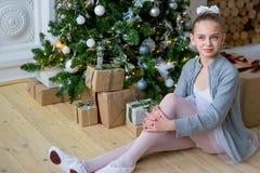 Junger Balletttänzer, der nahe Weihnachtsbaum sitzt Lizenzfreie Stockbilder