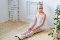Junger Balletttänzer, der nahe Weihnachtsbaum sitzt Lizenzfreies Stockbild