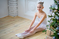 Junger Balletttänzer, der nahe Weihnachtsbaum sitzt Lizenzfreie Stockfotografie