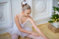 Junger Balletttänzer, der nahe Weihnachtsbaum sitzt Lizenzfreies Stockfoto