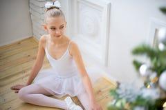 Junger Balletttänzer, der nahe Weihnachtsbaum sitzt Stockfotos