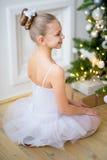 Junger Balletttänzer, der nahe Weihnachtsbaum sitzt Stockfoto