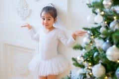 Junger Balletttänzer, der nahen Weihnachtsbaum steht Stockfoto