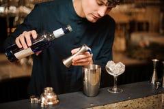 Junger Barmixer, der blauen Alkohol in einen Schüttel-Apparat für die Herstellung eines frischen Sommercocktails gießt Lizenzfreie Stockbilder