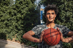 Junger Basketball-Spieler, der einen Ball auf Gericht im Freien hält Stockfoto