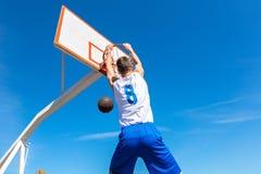 Junger Basketballstraßenspieler, der Slam Dunk macht Stockbild