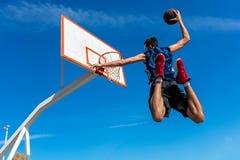 Junger Basketballstraßenspieler, der Slam Dunk macht Lizenzfreie Stockbilder