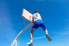 Junger Basketballstraßenspieler, der Slam Dunk macht Lizenzfreies Stockfoto