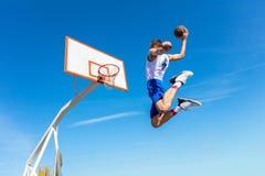Junger Basketballstraßenspieler, der Slam Dunk macht Stockfoto