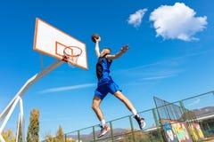 Junger Basketballstraßenspieler, der Slam Dunk macht Stockbilder