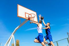 Junger Basketballstraßenspieler, der Slam Dunk macht Stockfotografie